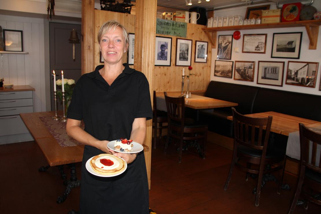 Servitør Solveig Midtbø i restauranten med kake og lapper.