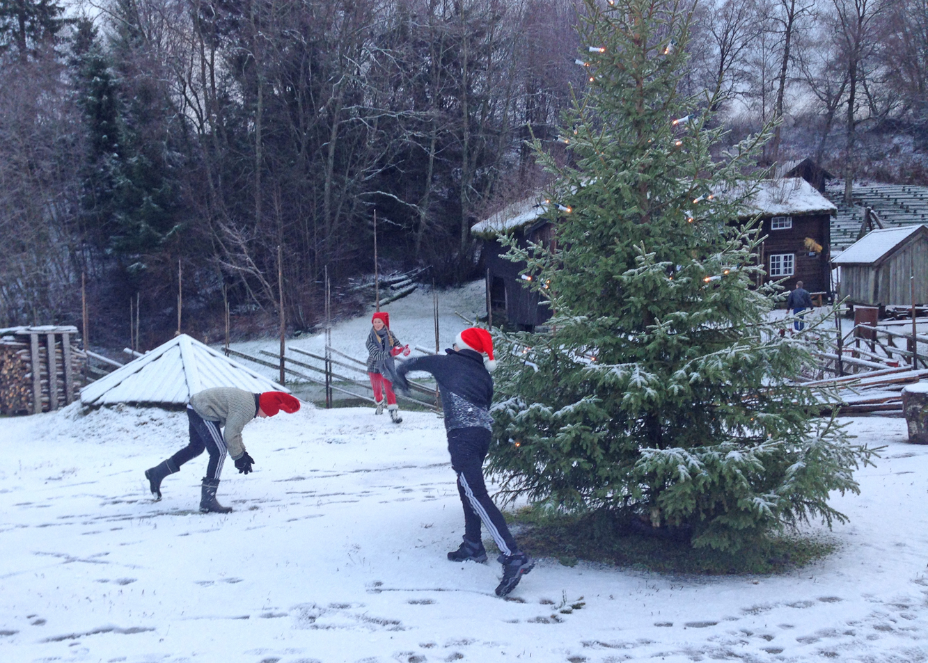 Nissebarna har det artig med snøballkrig rundt treet.