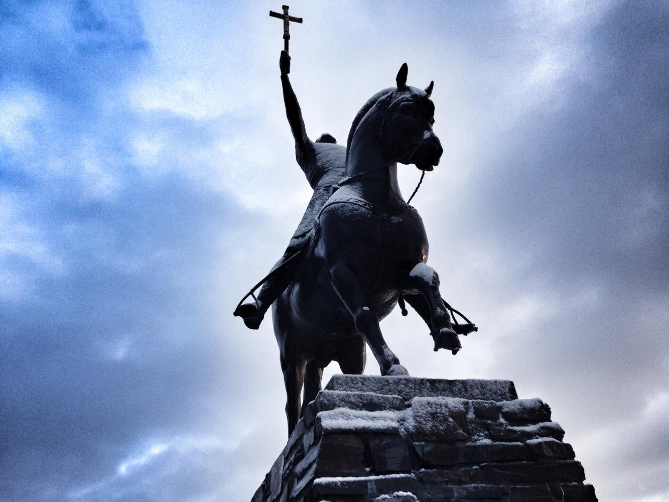 Dyre Vaas staue av Olav den hellige som løfter korste mot soleglad.