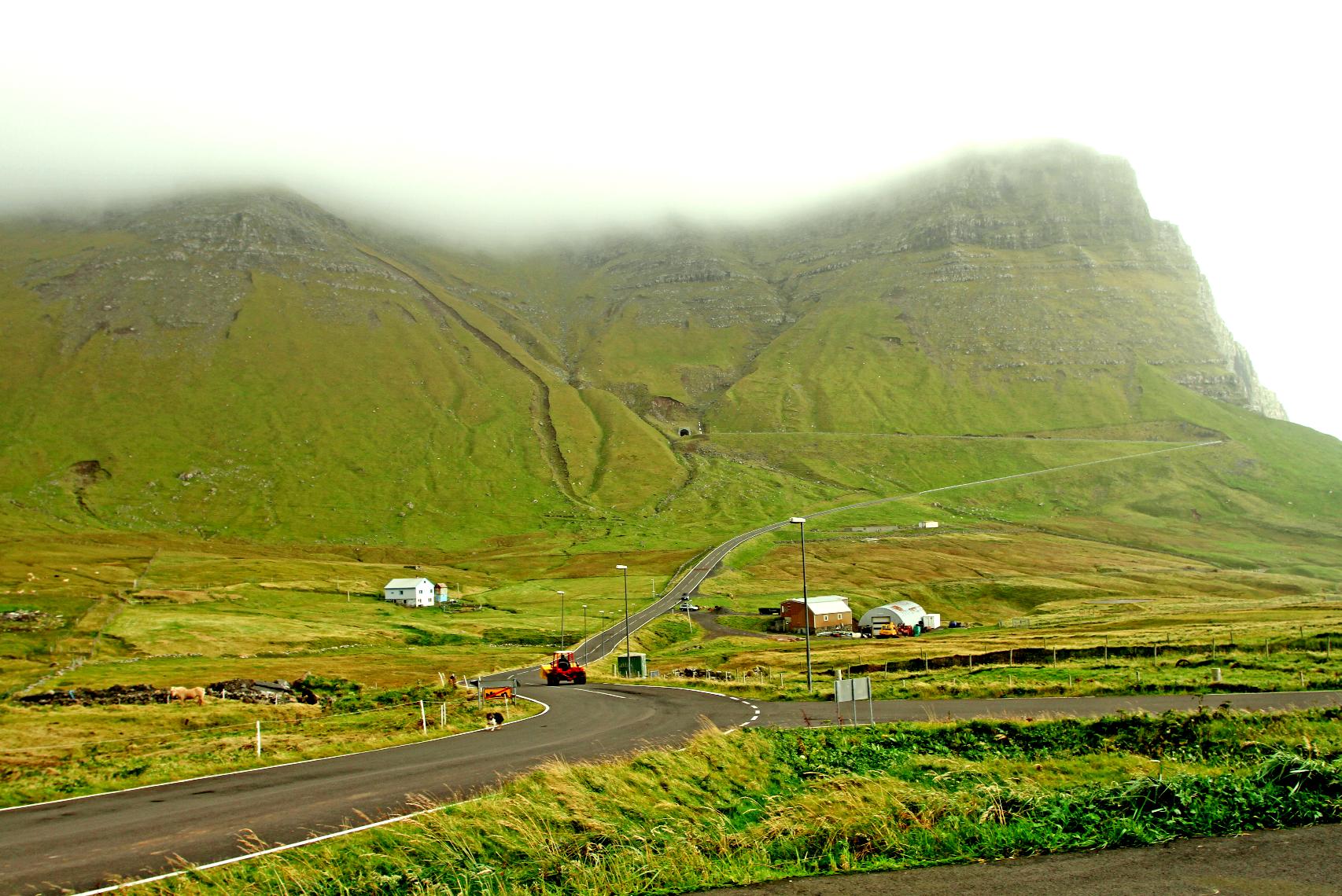 Tidligere måtte man ta bena fatt over fjellet for å komme til sivilasjonen. Nå går det tunnel fra Bøer til Gasadalur. Den lille åpningen sees midt i bildet.