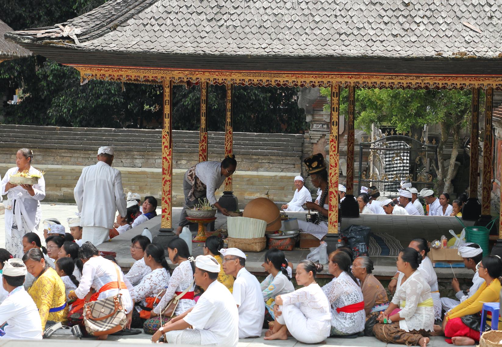 Balinesere samlet til bønn. Legg merke til presten under taket.