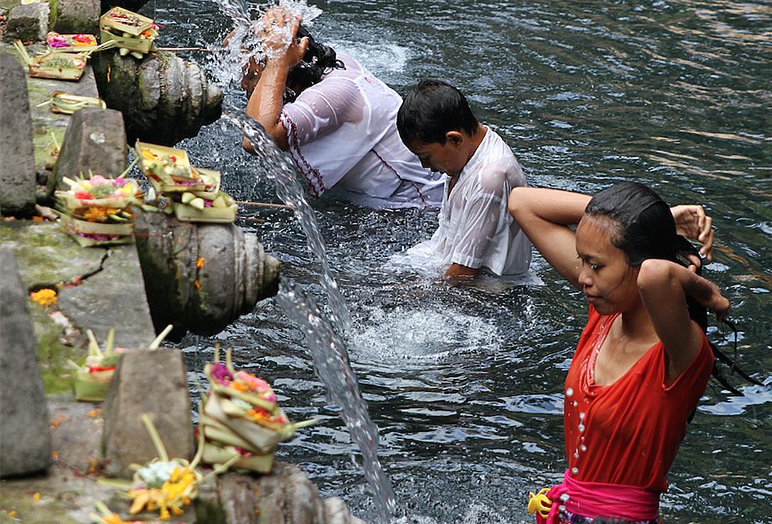 Badende hinduer i det hellige kildevannet ved Pura Tirta Empul på Bali.