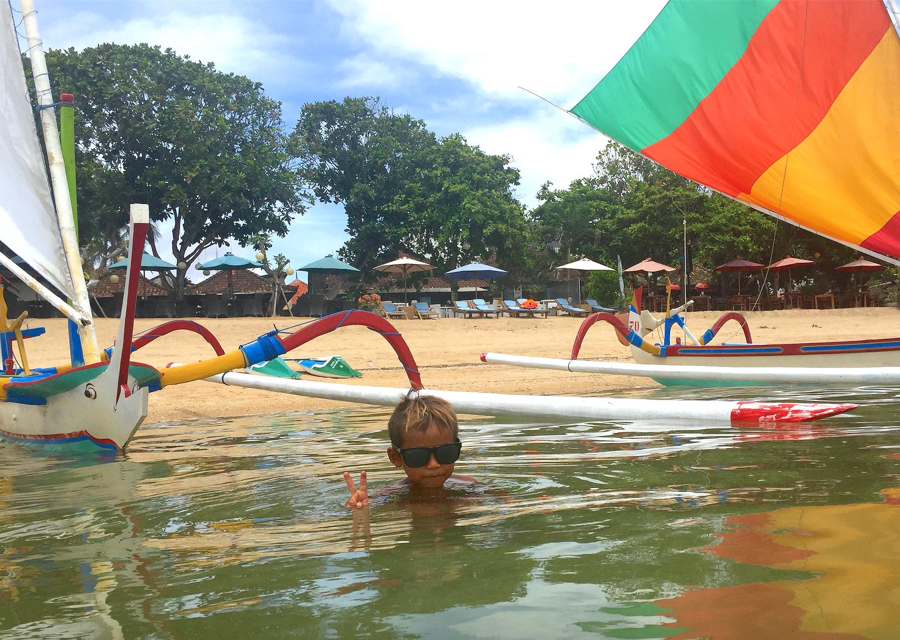 En kommende jukungskipper poserer foran kanoene på stranden.