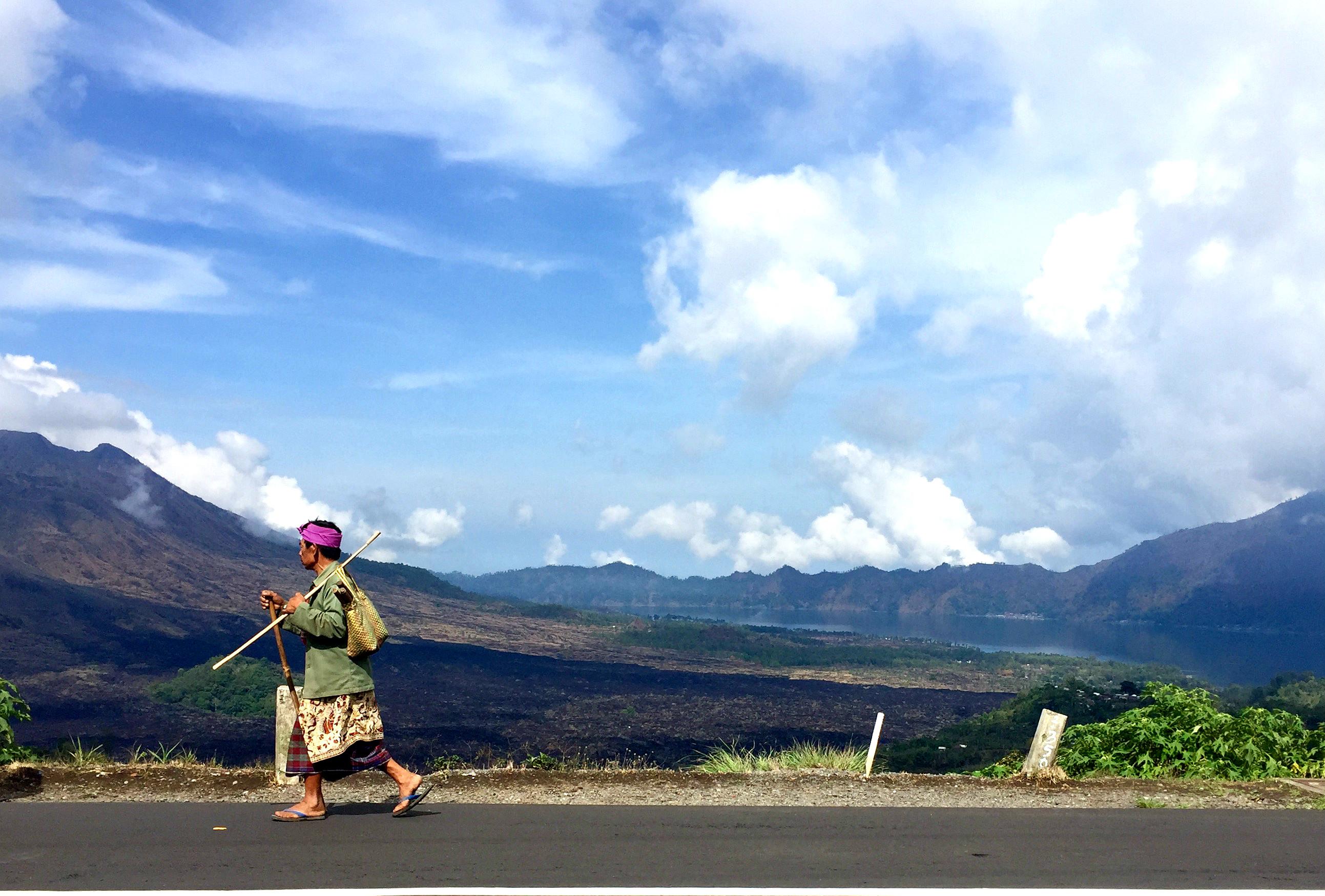En lokal mann til fots i Kitamani, med vulkanen Batur i bakgrunnen.