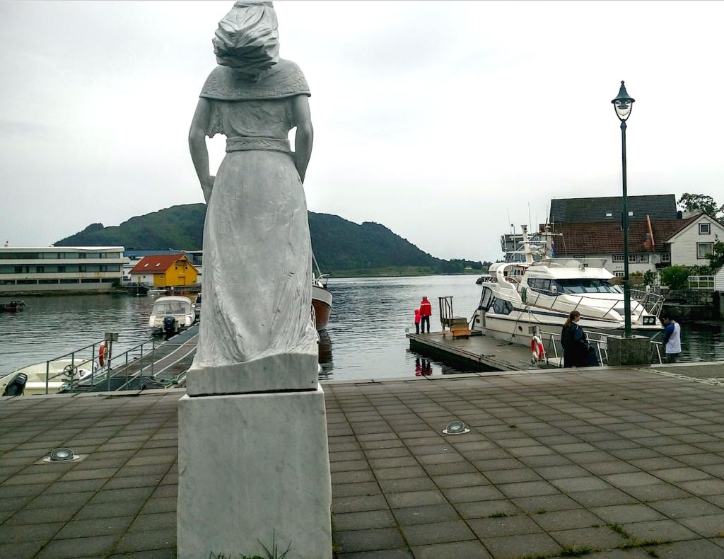 Sankt Sunniva-statuen i havnen i Selj. bakfra. Forut er øya Selja hvor klosterruinene ligger.
