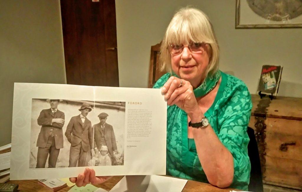 HOLMSBUMALERNE: Hilde Egner med bilde av de tre holmsbumalerne som galleriet er bygget etter.