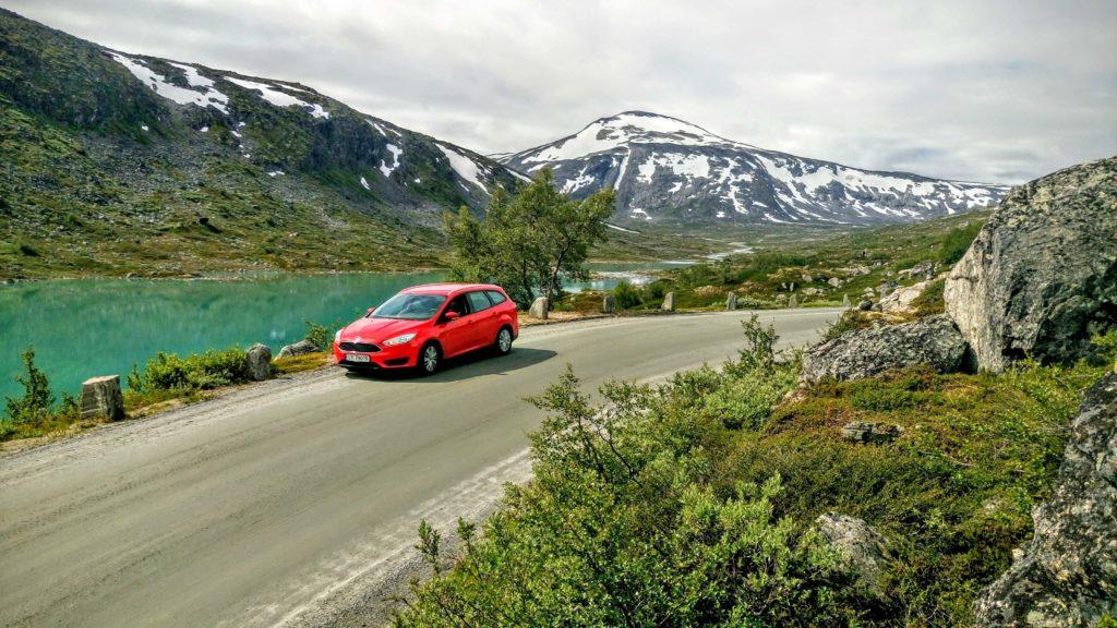 CA MIDTVEIS: Den røde bilen tar seg godt ut mot det irrgrønne vannet og fjellene bak.
